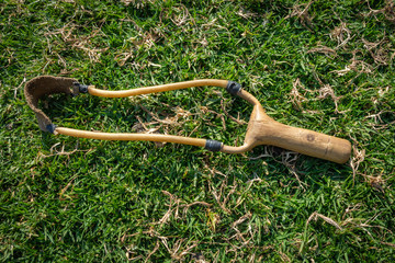 handmade wooden slingshot weapon in the grass