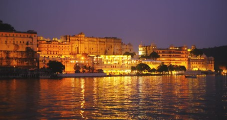 Fotomurales - Udaipur City Palace and Lal ghat on bank of lake Pichola with water ripples - Rajput architecture of Mewar dynasty rulers of Rajasthan. Sunset at Udaipur, India.