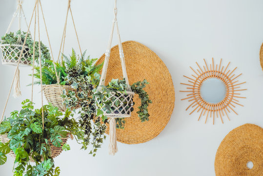 Modern minimal Scandinavian home interior design. Straw round decor with hanging flower pots with green plants on the white wall background. Eco natural trendy style. Copy space.