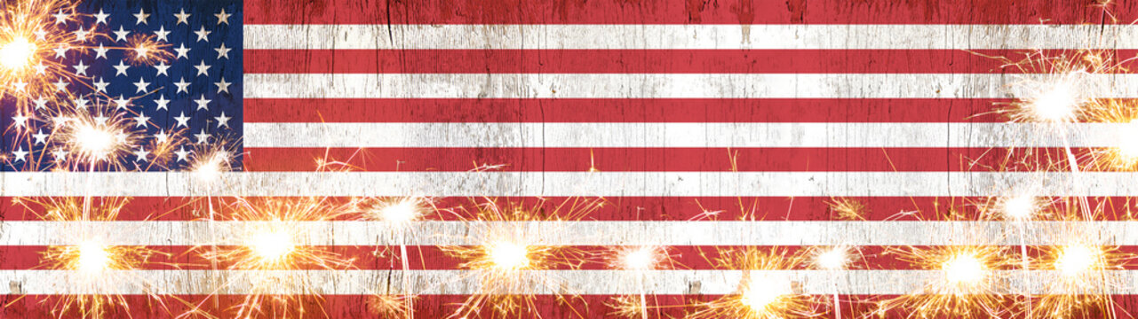 Happy 4th of July background panorama banner - American flag on wooden rustic vintage texture with sparklers and firework