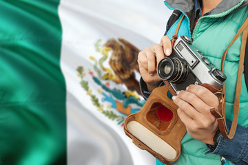 Mexico photographer concept. Close-up adult woman holding retro camera on national flag background. Adventure and traveler theme.