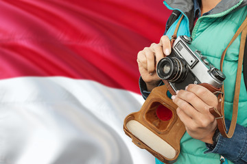 Monaco photographer concept. Close-up adult woman holding retro camera on national flag background. Adventure and traveler theme.