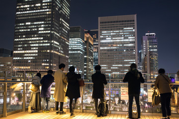 People enjoying night view of Marunouchi District from rooftop garden of Kitte nearby Tokyo Railway Station KITTE丸の内からビル群の夜景を観る人々 東京駅