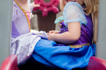 young girls in princesss dresses play together on toy