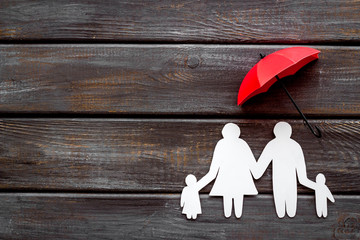 Live insurance concept. Family silhouette protected by umbrella on dark wooden background top-down copy space