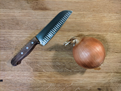 Sweet Yellow Onion and a Large Kitchen Knife with Wooden Handle