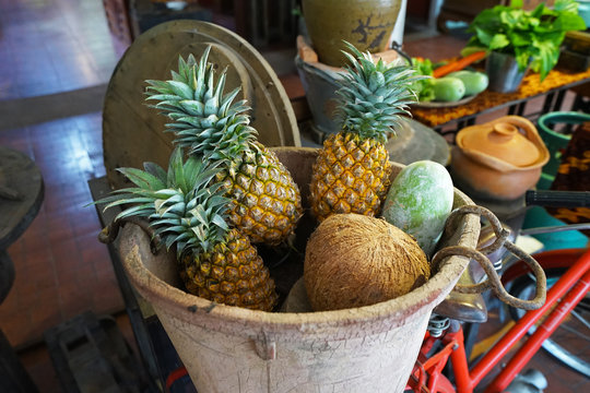 Clay pot fulled of pineapples, mango and coconut fruits