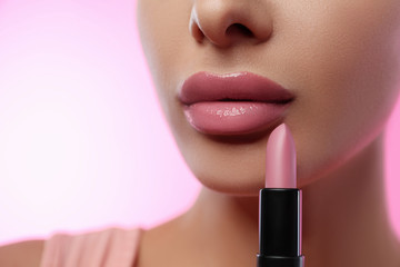 Woman with glossy lipstick on pink background, closeup Wall mural