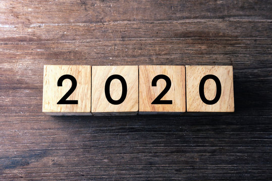 Top view text 2020 on wood cube which lay on wood table.