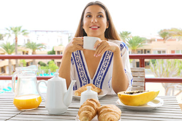 Happy smiling young woman eating breakfast in her vacation resort hotel view from outside private balcony