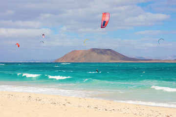 Beautiful view of Corralejo Dunas beach with Lobos Island and kitesurfers, Fuerteventura, Canary Islands