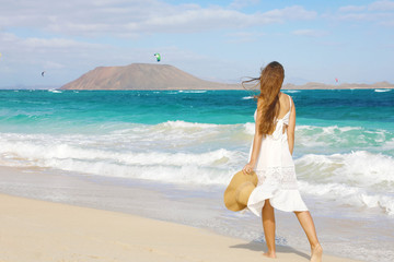 Young woman walking on Corralejo wild beach looking at Lobos Island on the background, Fuerteventura, Canary Islands