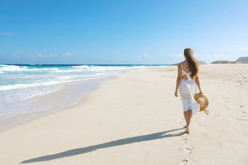 Foto op Aluminium Canarische Eilanden Young woman walking on empty wild beach with white sand and blue sky in Corralejo, Canary Islands