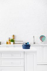 selective focus of blue pot and minimalistic modern white kitchen interior with kitchenware and...