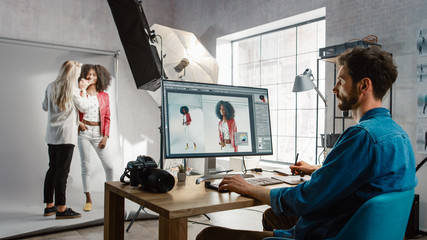 Backstage of the Photoshoot: Make-up Artist Applies Makeup on Beautiful Black Girl. Photo Editor Works on Desktop Computer Retouching Photo with Image Editing Software. Fashion Magazine