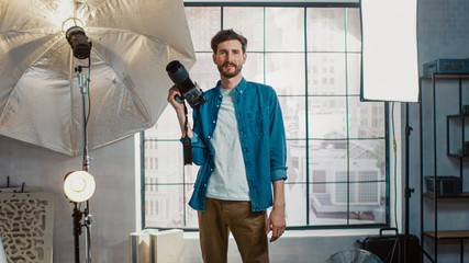 In the Photo Studio with Professional Equipment: Portrait of the Handsome Photographer Holding State of the Art Camera Ready to Take Pictures with Softboxes Lighting in Background