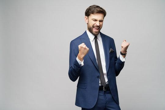 Very happy successful winner gesturing businessman over grey background