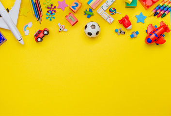 Frame of kids toys on yellow background with copy space