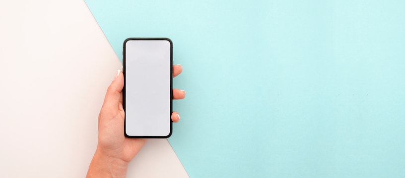 Woman hand holding the black smartphone with big blank screen and modern frame less design. Top view travel mockup horizontal banner