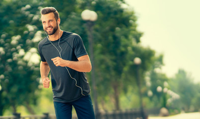 Photo sur Aluminium Jogging Young happy cheerful smiling bearded man, during morning jogging outdoors. Fitness, sport, exercising, crossfit and workout concept.