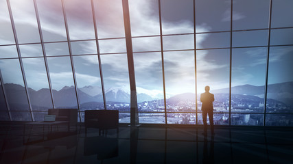 Businessman stands in a huge office with mountain view.