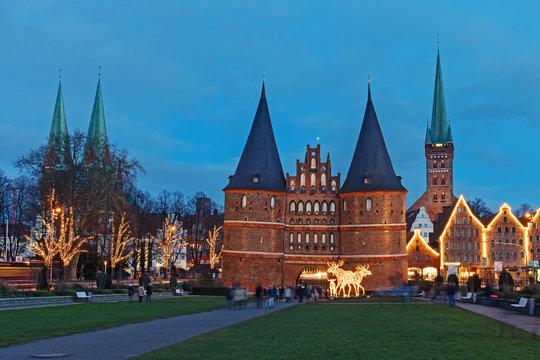 Blick auf die Altstadt von Lübeck mit dem Holstentor, der Marienkirche (links), der Petrikirche und historischen Salzspeichern zu Weihnachten