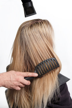 Professional hairdresser with hairdryer and hairbrush drying fem.
