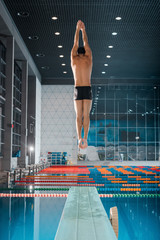 back view of swimmer in swimming cap jumping into water