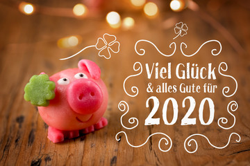 New year card 2020, german language - Good luck and best wishes for 2020 - Good luck symbol - Marzipan pig on rustic wooden background