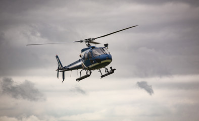 Blue helicopter in flight over gray sky