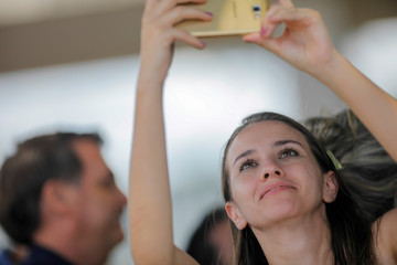A woman takes a picture of the Brazil's President Jair Bolsonaro outside the Alvorada Palace in Brasilia