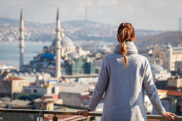 Beautiful woman stands at the rooftop an looking on popular New mosque, Istanbul, Turkey
