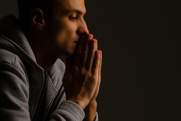 Religious young man praying to God on dark background, black and white effect Papier Peint