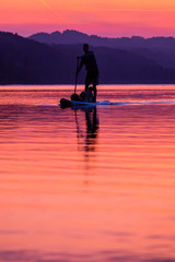 Acrylic Prints Coral silhouette of a paddling man on a lake at sunset
