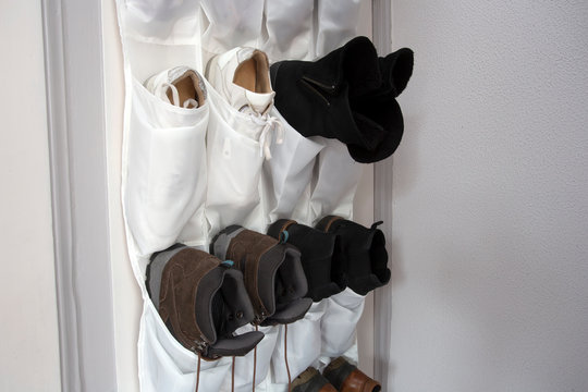 Shoe rack hanging on a wooden door, storage for shoes