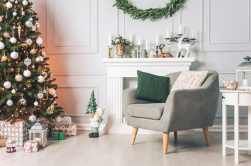 Classic interior with an armchair tables, and a Christmas tree with decorations on a light background of a wall with a fireplace.