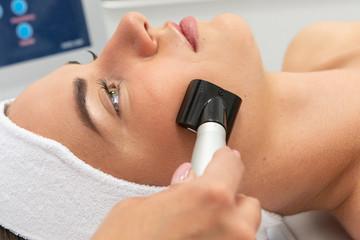 Fototapeta Młoda kobieta, zbliżenie na twarz podczas zabiegu specjalistycznym urządzeniem w salonie urody. Kuracja przeciwzmarszczkowa.  obraz