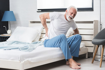Senior man suffering from pain at home