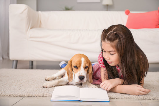 Little Asian girl with cute beagle dog reading book at home