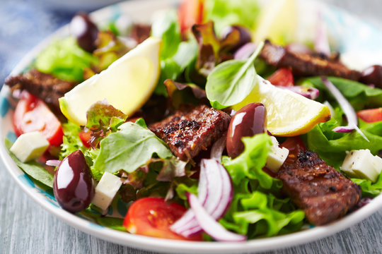 Tasty salad with grilled beef steak, cherry tomatoes and lettuce. White wooden background. Close up.