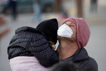 A migrant carrying his daughter prays at the government-run Leona Vicario migrant shelter, temporarily closed by health authorities following a varicela outbreak between Central American migrants, in Ciudad Juarez