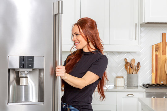 A woman looks inside a refrigerator in a beautiful modern farmhouse kitchen