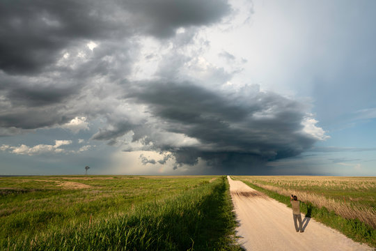 A man photographing a supercell storm in wheat field