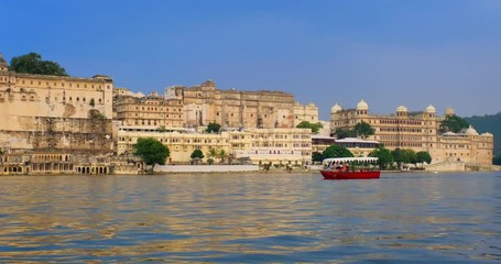 Wall Mural - Udaipur City Palace on lake Pichola with tourist boat - Rajput architecture of Mewar dynasty rulers of Rajasthan. Udaipur, India
