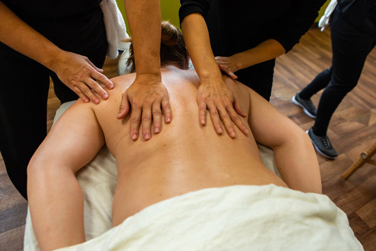 A close up and high angle view on the bare back of a woman as two massage students practice bodywork techniques during training exercise, with copy space