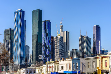 Melbourne, Victoria, Australia, October 25, 2018: Melbourne city skyline with some buildings under construction rising above the older buildings of North Melbourne, against a clear blue sky.