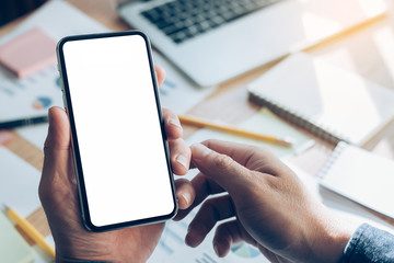 Mockup image blank white screen cell phone.man hand holding texting using mobile on desk at home office.background empty space for advertise text.people contact marketing business,technology