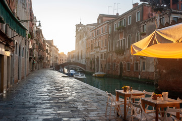 Venetian channel in the morning. Embankment and a street cafe in the light of the rising sun Fotomurales