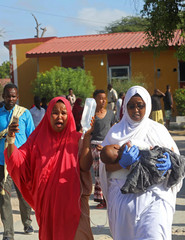 A woman reacts as her injured child is assisted at the Madina hospital following a car bomb explosion at a checkpoint in Mogadishu