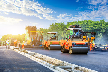 Fototapeta Construction site is laying new asphalt road pavement,road construction workers and road construction machinery scene. obraz